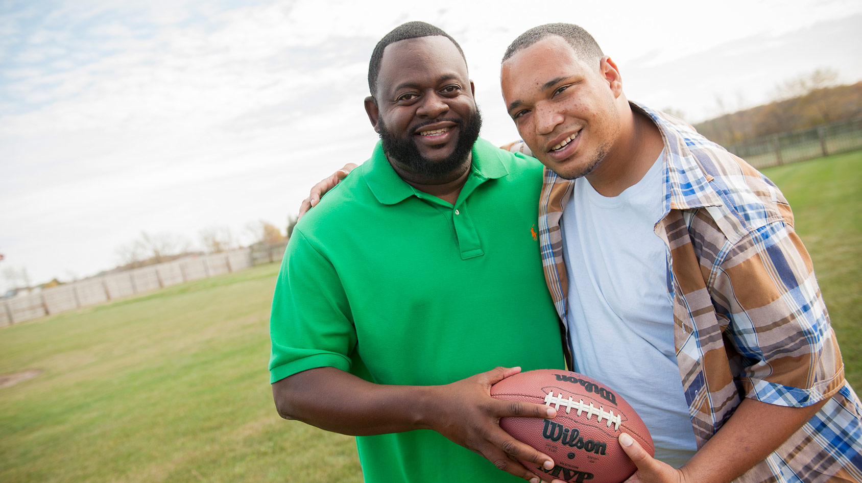 Two Men Smiling With Football